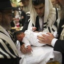 (An ultra-Orthodox Jewish father (C) holds his son before his circumcision in Jerusalem September 24, 2012. REUTERS/Ronen Zvulun )