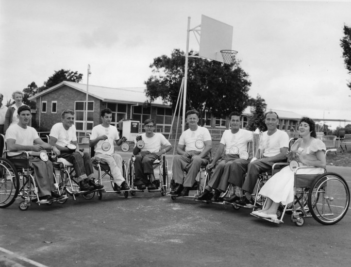 """Physiotherapist Eileen Perrottet at back with medallists at the first Sports Day at Mt Wilga Rehabilitation Hospital 1959,"" 1959, by John Sherwell. Used under a Creative Commons Attribution-Share Alike 3.0 Unported license by the Australian Paralympic Committee."