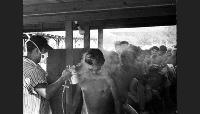 """Bracero workers being fumigated,"" 1956. Photograph by Leonard Nadel, NMAH, History of Technology Collections."