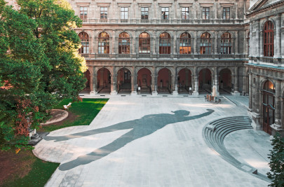Photo of a large plaza with a large art installation depicting a woman's shadow